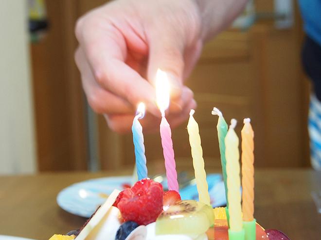 誕生日のケーキにろうそくを灯す